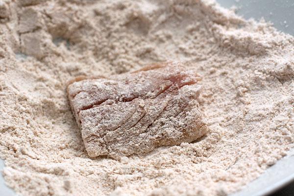 В тарелке смешайте муку с солью. Филе скумбрии разрежьте на порционные куски и обваляйте в мучной смеси.