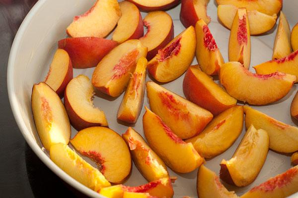 Форму для выпечки смажьте маслом и равномерно разложите в ней дольки персиков.