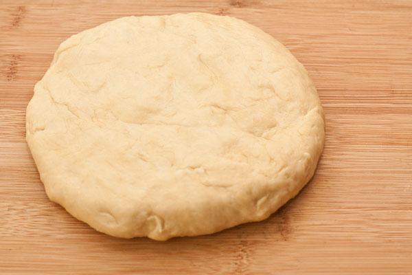 Тесто тщательно вымесите на менее 10 минут на смазанной маслом рабочей поверхности. Чем интенсивнее вы будете месить тесто, тем более эластичным оно получится.  После вымешивания заверните тесто в пленку и дайте выстояться не менее получаса.