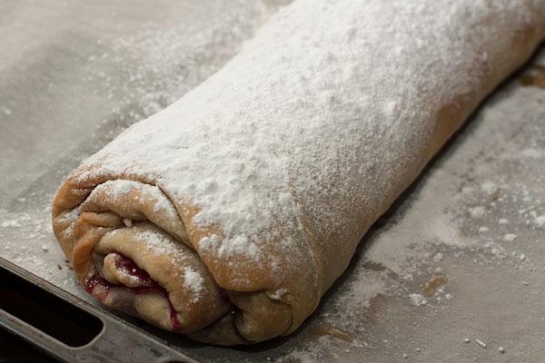Теплый штрудель  равномерно и густо посыпьте штрудель сахарной пудрой с помощью сита.