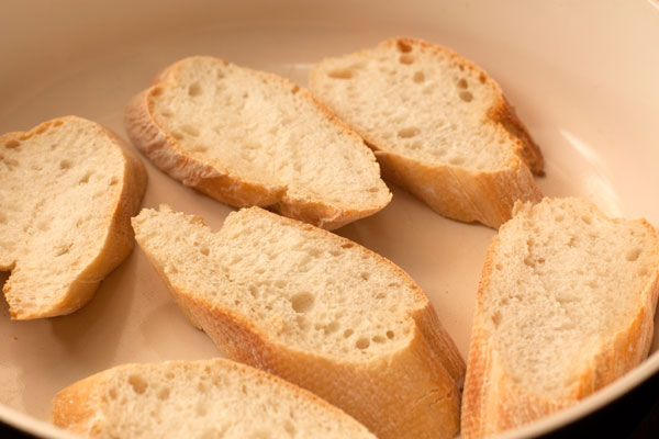 Свежий хлеб нарежьте довольно толстыми ломтиками и поджарьте на сухой горячей сковороде по 1 минуте с каждой стороны так, чтобы получилась подсушенная корочка, а внутри хлеб остался мягким.