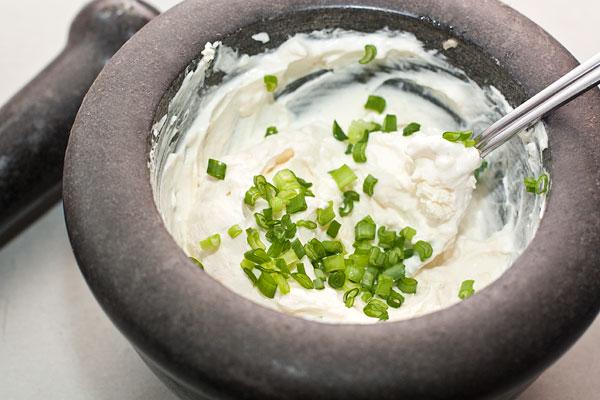Пока батат запекается, сделайте сырный крем.   Для этого в ступке разотрите мелко нарезанный чеснок с добавлением морской соли. Когда получится однородная кашица, добавьте сыр и мелко нарезанный зеленый лук. Хорошо перемешайте.
