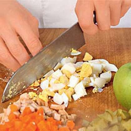 Затем необходимо картофель, лук, яйца и яблоко, соленые огурцы и вареную колбасу нарезать небольшого размера кубиками.