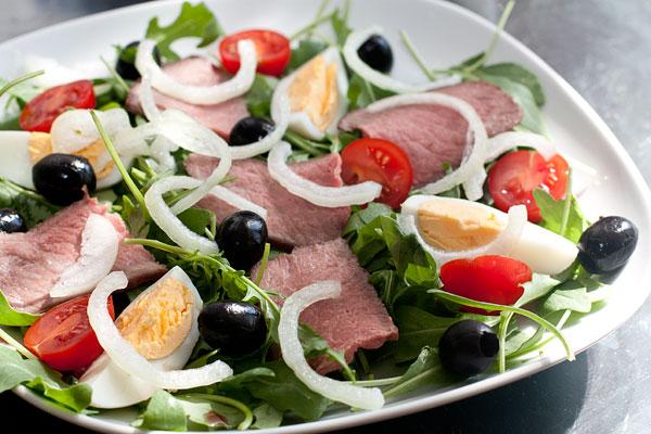На рукколу положите ломтики говядины и подмаринованный лук, предварительно дав хорошо стечь маринаду. Добавьте разрезанные пополам черри и украсьте маслинами.