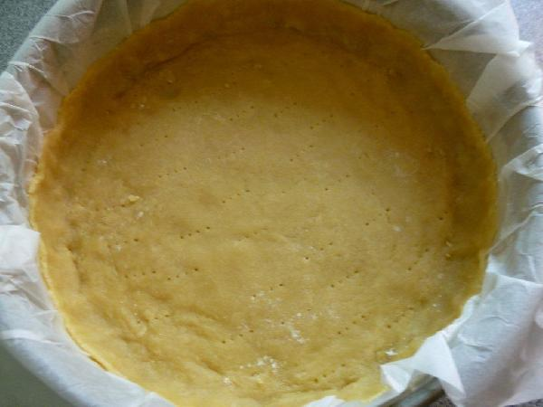 Охлажденное тесто раскатываем на бумаге для выпечки  - так его легче будет потом укладывать в форму для выпечки. Вам понадобиться форма диаметром 28 см. В форме обрезаем бортики, оставив высоту 2-2,5 см. Накалываем тесто в нескольких местах вилкой и ставим в разогретую до 200 градусов духовку. Выпекаем 15 минут. Для того, чтобы тесто не стало слишком сухим, его можно накрыть сверху бумагой для выпечки.