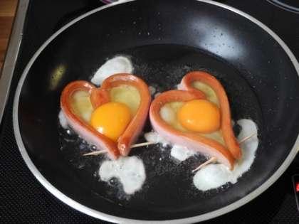 Разбить яйца аккуратно внутрь сердечек, посолить, поперчить,закрыть крышкой.Жарить на среднем огне, пока желток и белок не запекутся