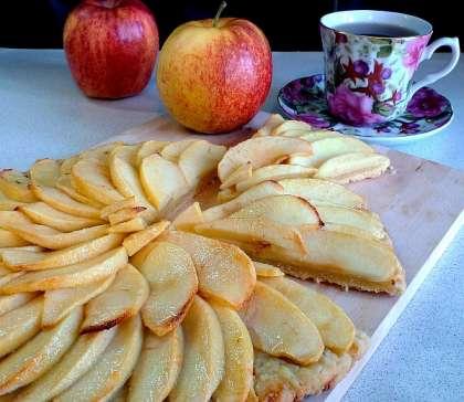Кистью смазать яблоки масляно-сахарной смесью, посыпать 1ст.л. сахарной пудры.    Выпекать в разогретой до 220градС духовке 10минут, затем смазать и присыпать яблоки ещё раз и выпекать при 190град ещё 20минут (до полной мягкости яблок).  Вынуть пирог из духовки и дать немного остыть. Посыпать сахарной пудрой и подавать теплым.