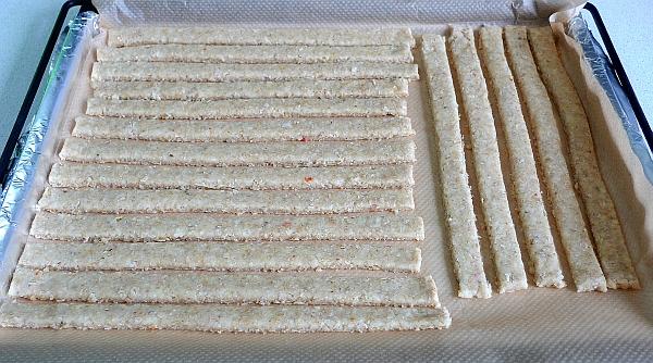 Противень застелить пергаментной бумагой и при необходимости смазать растительным маслом.  Разложить палочки на противне и выпекать в нагретой до 190градС духовке в течение 10-12минут (до золотистого цвета).