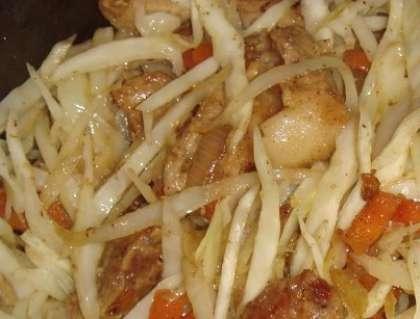 Затем выложите ее в казанок к мясу и овощам. Перемешайте и тушите еще минут двадцать. Помешивайте, чтобы капуста не пригорела.