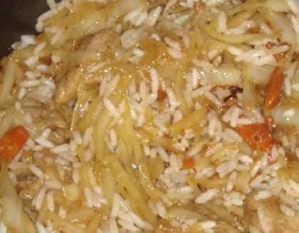 Рис промойте в проточной воде (пять-семь раз). Пересыпьте рис в кастрюльку и залейте водой. Отварите крупу до полуготовности, немного присолите. Снимите. Затем выложите в казанок. Перемешайте. Продолжайте тушить около десяти минут. Добавьте лавровый лист и другие специи на свой вкус.