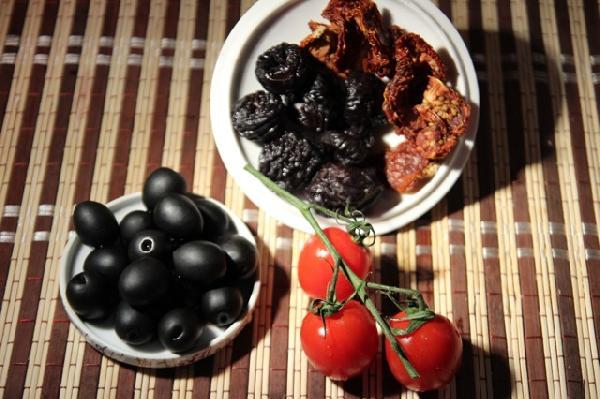 """Далее самый интересный этап - в ход идут ингредиенты, обычно не допускающиеся к борщам, а именно - маслины (можно с косточками, если любите их вынимать), чернослив (желательно пожирнее), вяленые томаты (придающие всему блюду сложно определимое словами, но интересное звучание), аджика (я использую магазинную аджику по-грузински). Если на вкус маслины сами по себе сочные и нежные - можно добавить в бульон немного """"воды"""", в которой они плавали в банке. И помидорки черри или пару томатов в собственном соку, с которых нужно снять кожу. Все это вместе добавляем в наш кипящий бульон (ингредиенты не режем, оставляем целыми)."""