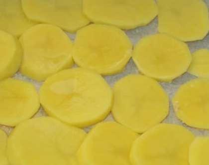 Клубни картофеля следует почистить, помыть. Обсушенный слегка картофель порежьте ломтиками. Смотрите, чтобы они были примерно одинаковой толщины (до 0,5 см).
