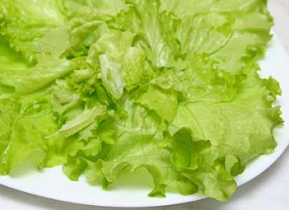 Листья салата вымойте и обсушите салфеткой или бумажным полотенцем. Выложите листочки на порционные тарелки.