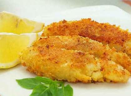 Каждое готовое обжаренное филе положите на порционную тарелку. Как украшение используйте кольца лимона и зелень.