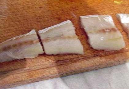 Филе минтая нужно разморозить. Промыть рыбу и хорошо обсушить. Разрежьте филе рыбы на куски (порционные). Посолите. С одного лимона выдавите сок в отдельную емкость. Полейте рыбу лимонным соком. Оставьте ее мариноваться так где-то на полчаса.