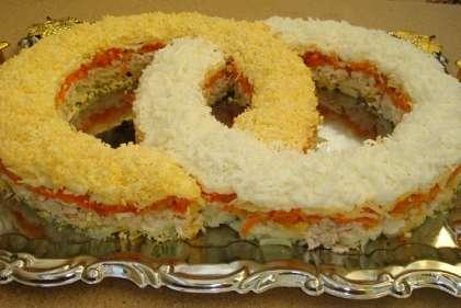 В красивом блюде сформируйте салат в форме колец. Выкладывайте салат в такой последовательности: картофель тертый (посолить чуть-чуть), майонез. Сверху положите кубики куриного филе плюс майонез, дальше жареная морковь с луком, опять майонез. Потом идет слой сыра с майонезом. И последнее, это завершите кольца, на одно белок выложите слоем, а на другое – желток. Салат на свадьбу можно подавать к столу.