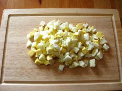 Возьмите яйца. Отварите их в кипящей воде 4-6 минут. Яйца нужны вкрутую. Подержите их в холодной воде и очистите от шкарлупы. Мелко порубите.