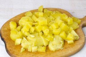 Картофель промойте. Воду для варки посолите. Отварите в клубни в мундирах. Обдайте картофель холодной водой, и кожура будет легче отходить. Почистите и порежьте готовый картофель кубиками.