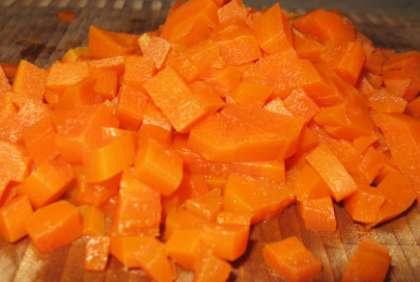 Возьмите морковь. Вымойте и также  отварите в кожуре. Положите морковь на несколько минут в холодную воду. Почистите. Затем нарежьте морковь мелкими кубиками.