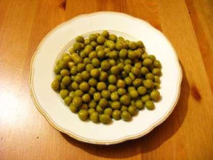 Откройте банку с зеленым горошком. Возьмите необходимое количество для салата и откиньте на сито. Лишняя водя с горошка должна стечь.