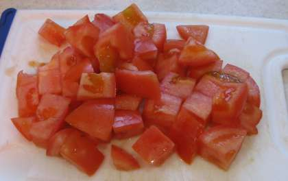 Возьмите красные помидоры. Вымойте. Затем порежьте на крупные кубики.