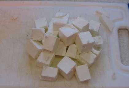 Следующим этапом будет нарезка сыра. Возьмите сыр «Фета», разрежьте на брусочки, а потом на мелкие кубики.