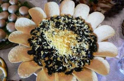 Откройте банку с кукурузой и присыпьте верх салата. По верх кукурузы рисуем решетку из ромбиков. На нее выкладываем мелко порезанные маслины, они будут выглядеть как семечки. В конце нарежьте кружочками огурцы. Выложите их на край тарелки, а поверх накройте чипсами. Салат готовиться непосредственно перед подачей на стол.