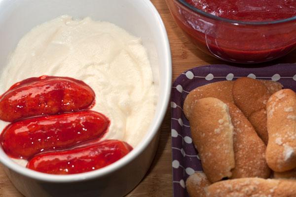В большую форму или маленькие порционные формочки положите немного крема (1,5-2 см).  Савоярди по одному окунайте с обеих сторон в клубничную пропитку, и плотно выкладывайте поверх крема.