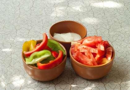 Прежде всего надо подготовить овощи. Нарезать перец произвольно (венгры режут листочками), нарезать дольками помидор (если он домашний и шкурка тоненькая, можно со шкуркой, если толстая шкурка, очистить отнее). Лук нарезать полукольцами.