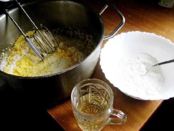 Муку добавлять в приготовленную массу двумя равными частями. Тщательно перемешивая, периодически подливать в тесто вино.