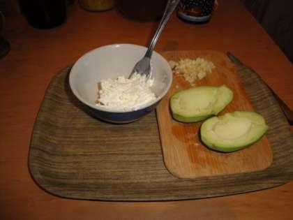 Сыр выложить в тарелку. Чеснок почистить и порезать. Авокадо очистить и вынуть косточку