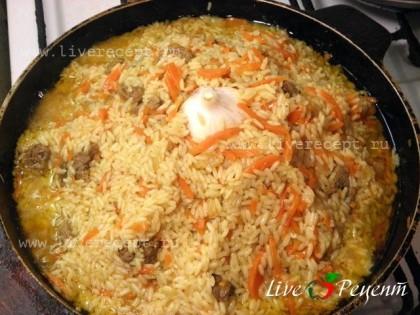 Через 15-20 минут открываем казан, собираем рис горкой и сверху кладем головку чеснока, хорошо вдавив ее в рис. Закрываем крышку и варим до готовности риса еще  10-15 минут.