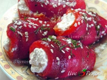 Перед подачей рулетики из сладкого перца с козьим сыром сбрызгиваем оливковым маслом, немного посыпаем зеленью и кунжутом.