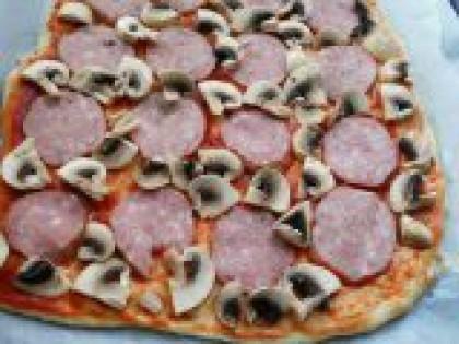 3 Выложить колбасу и грибы. Колбасу порезать тонкими кружочками, грибы - кусочками. Выложить равномерно по всему тесту колбасу и грибы.