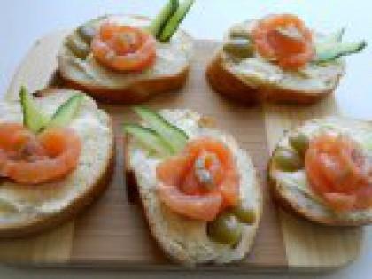 """5 Выложить кусочки огурца и оливок. Свежий огурец порезать кружочками, затем каждый кружочек еще пополам. Выложить на бутерброд рядом с """"розочкой"""" в виде листочков. Оливки порезать кружками (у меня были зеленые оливки с косточкой, поэтому я просто отрезала кусочки) и выложить на бутерброд с другой стороны """"розочки""""."""