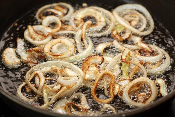 В глубокой толстостенной сковороде (идеально, конечно, если есть казан) на большом огне разогрейте растительное масло. Температура масла должна быть такой, чтобы лук, опущенный в него, начинал довольно интенсивно шипеть.  Обжаривайте лук до золотисто-коричневого цвета, чтобы из него ушла лишняя влага.