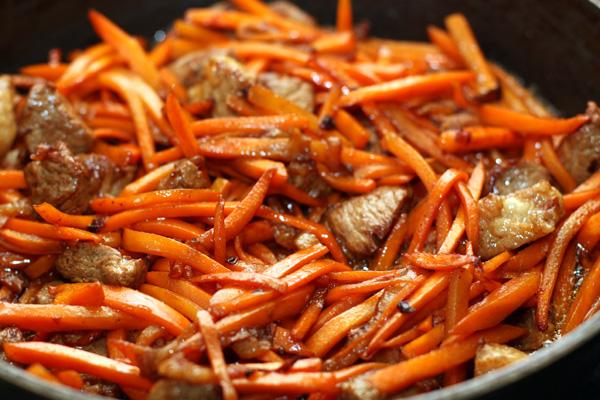 Когда мясо немного обжарится (7-8 минут), добавляйте морковь. Готовьте еще 5 минут до мягкости моркови.