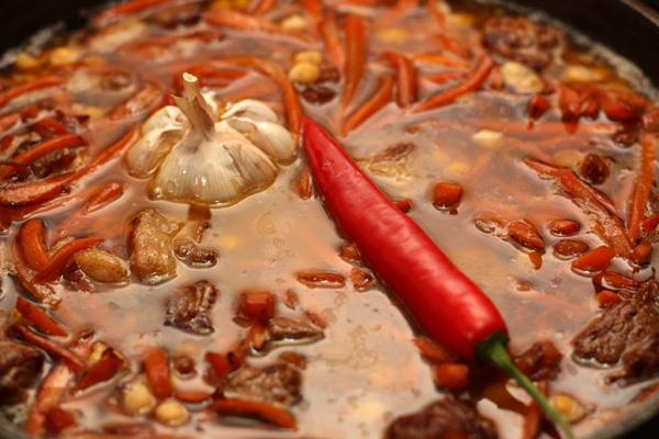 Налейте воды так, чтобы она покрывала мясо. Вставьте в середину целый чеснок, очищенный от верхней шелухи и корешков и острый перец.