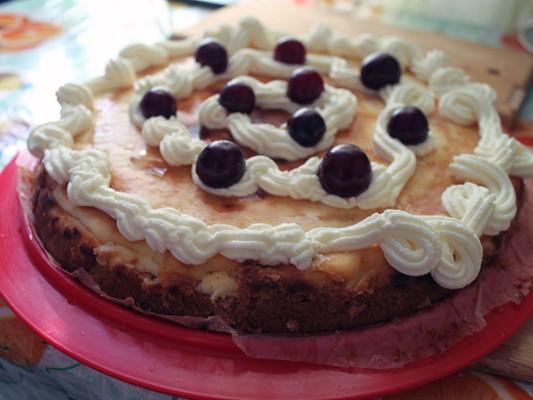 """Остывший пирог украсить взбитыми сливками и отложенной ранее вишней.  Взбитые сливки приготовим сами: для этого взобъём холодные сливки до образования нужной консистенции. Взбитые сливки положить в кондитерский шприц/мешочек и сделать """"волну"""" вдоль края торта. Выложить вишенки."""