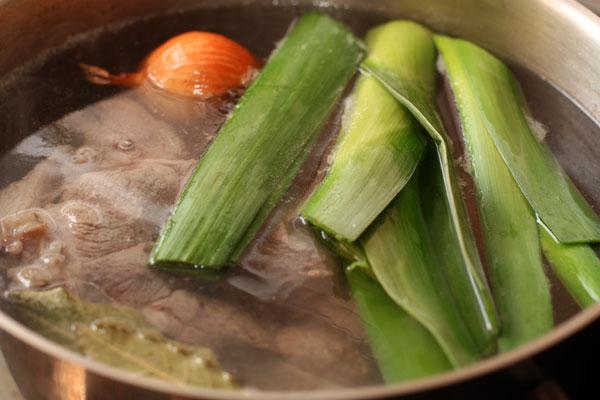 Когда пена перестанет образовываться, положите в бульон овощи и специи и варите на небольшом огне 1 час.