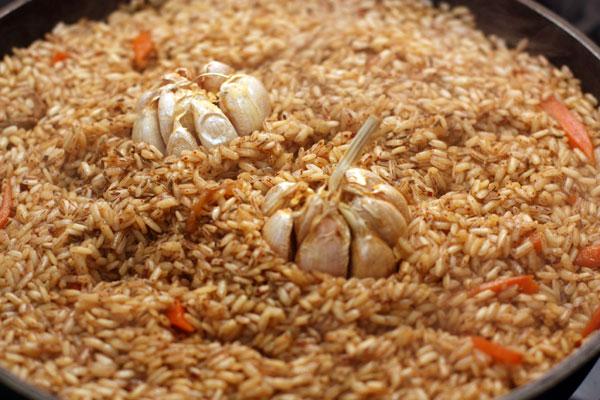 Когда основная часть воды впитается, возвращаем чеснок в середину, посыпаем рис слегка растертой зирой и плотно закрываем крышкой. Если плотной крышки нет, можно накрыть плов перевернутым блюдом, а уже сверху крышкой.