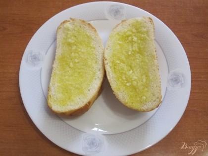 Шаг 2 Булочку разрезать горизонтально пополам. Натереть обе половинки оливковым маслом и чесноком, пропущенным через пресс.