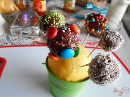 Теперь все шарики обваливаем в любой посыпке. Я использовала кокосовую стружку, посыпку кондитерскую и даже драже. Покрытые посыпкой конфеты насаживаем на зубочистки и втыкаем их в лимон или другой твердый фрукт. Даем конфетам застыть в течении 2-3 часов.