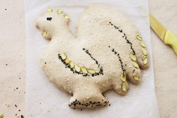 Смажьте пирог желтком, смешанным со столовой ложкой воды. Украсьте петуха разными семенами или орехами. Подойдут семена подсолнечника, тыквы, кунжута, мак, фисташки, миндаль. Всё, что найдётся в доме.