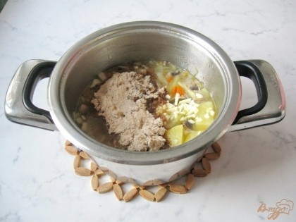 Снимаем с огня варившиеся овощи. Выкладываем в кастрюлю тушёные с луком и кореньями грибы. Добавляем поджаренную муку и чеснок.Солим и перемешиваем.