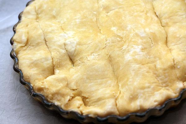 Накройте пирог тестом, подворачивая края внутрь формы.