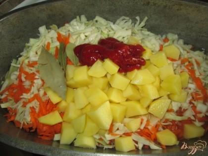 Сложить в казан нашинкованную капусту, морковь, картофель, томатную пасту, лавровый лист.