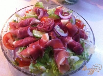 Выкладываем на плоскую тарелку салат и сверху рулетики с прошутто. Поливам оставшейся заправкой.